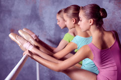 Ballerinas stretching on the bar Stock Photos