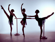 Ballerinas stretching on the bar Stock Images