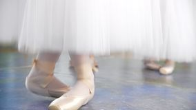 Ballerinas in white tutus bounce up on pointe shoes in a studio stock video