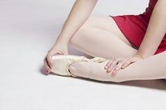 Ballerinasammanträde på ett vitt golv som trycker på hennes fot royaltyfri fotografi