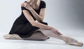 Ballerinasammanträde på golvet royaltyfri fotografi