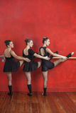 Ballerine che praticano a Barre Against Red Wall Fotografie Stock