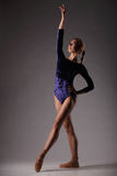 Ballerine dans l'équipement bleu posant, jeune belle femme mince sur le fond gris de studio Photographie stock libre de droits