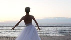 Ballerine de danse dans le tutu blanc et pointe sur le remblai au-dessus de l'océan au lever de soleil Jeune belle pratique en ma banque de vidéos