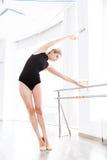 Ballerine de femme dansant près du bâton sur le mur à l'école de ballet Photo libre de droits
