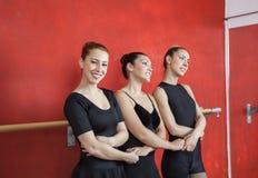 Ballerine de sourire tenant des mains d'amis dans le studio Photographie stock