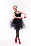 Ballerine féminine posant dans des chaussures blanches de tutu et de ballet sur le fond blanc Photos stock