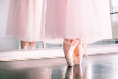 Ballerine feet in pointe shoes and pink airy tutu skirt reflected in a mirror of a dance hall stock images