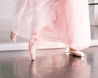 Ballerine feet in pointe shoes and pink airy tutu skirt reflected in a mirror of a dance hall royalty free stock photos