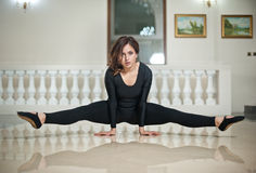 Ballerine gracieuse faisant les fentes sur le plancher de marbre Danseur classique magnifique exécutant une fente sur le plancher photographie stock