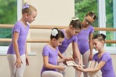 Ballerine lui montrant de nouvelles pantoufles de ballet aux amis Photos libres de droits