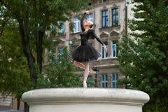 Ballerine magnifique dans la danse noire d'équipement dans les rues de ville photos stock