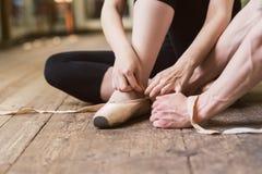 Ballerine mettant sur ses chaussures de ballet photos libres de droits
