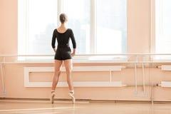 Ballerine se tenant sur le poite au barre dans la classe de ballet Image stock