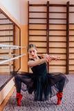 Ballerine utilisant le tutu noir faisant l'exercice dans le hall de formation Photographie stock
