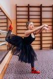 Ballerine utilisant le tutu noir faisant l'exercice dans le hall de formation Photographie stock libre de droits