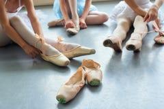 Ballerinen, die auf Pantoffel, geerntetes Bild sich setzen Lizenzfreie Stockfotografie