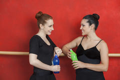 Ballerines tenant des bouteilles d'eau tout en regardant l'un l'autre Image libre de droits