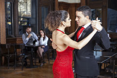 Ballerini appassionati di tango che eseguono mentre metà di coppie adulte Datin Immagini Stock
