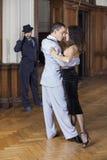 Ballerini appassionati di tango che eseguono mentre uomo che li esamina Fotografia Stock