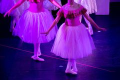 Ballerini di balletto nell'ambito di luce porpora con i vestiti classici che eseguono un balletto sul fondo della sfuocatura immagine stock libera da diritti