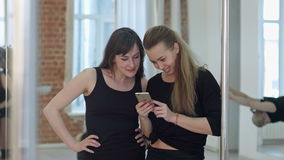 Ballerini felici svegli del palo che prendono una rottura dal loro allenamento e rete sociale con un telefono cellulare video d archivio