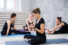 Ballerini o classe felici svegli di yoga che prende una rottura dal loro allenamento e rete sociale con un telefono cellulare Fotografia Stock