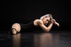 Ballerino atletico della donna che allunga sul nero Fotografia Stock Libera da Diritti