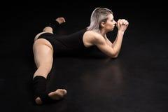 Ballerino atletico della donna che allunga sul nero Immagine Stock
