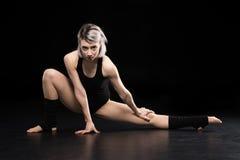 Ballerino atletico della donna che posa e che esamina macchina fotografica Immagini Stock