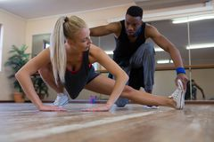 Ballerino che assiste amico femminile nell'allungamento sul pavimento Fotografia Stock Libera da Diritti