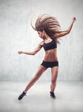 Ballerino della giovane donna con il fondo della parete di lerciume Fotografie Stock Libere da Diritti