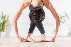 Ballerino di balletto castana esile professionista che posa sul fondo leggero in studio Giovane donna che fa allungando piegament Fotografia Stock