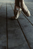 Ballerino di balletto che allunga sulle punte dei piedi nella stanza nera Fotografie Stock