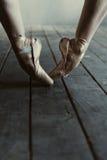 Ballerino di balletto che allunga sulle punte dei piedi nella stanza nera Immagini Stock