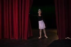 Ballerino di balletto che dà una occhiata tramite una tenda della fase Fotografia Stock