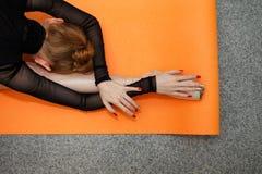 Ballerino di balletto che fa allungamento su una stuoia di yoga Immagine Stock Libera da Diritti