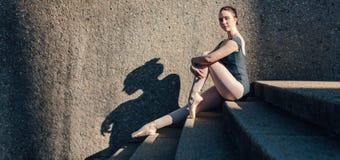 Ballerino di balletto che si siede sulle scale che indossano le scarpe del pointe Immagini Stock