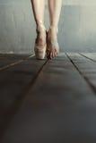 Ballerino di balletto che sta sulle punte dei piedi nella stanza nera Immagine Stock