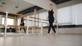 Ballerino di balletto classico grazioso in vestiti di sport che praticano stando spaccatura che allunga posizione alla sbarra di  archivi video