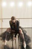 Ballerino di balletto contemporaneo su una sedia di legno su una ripetizione immagine stock