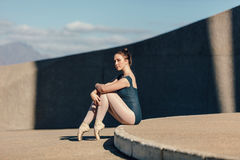 Ballerino di balletto femminile che si siede con garbo mentre riposando le sue dita del piede o Fotografie Stock