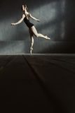Ballerino di balletto grazioso che sta sulla punta dei piedi nello studio Fotografia Stock