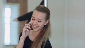 Ballerino felice del palo che chiama con un telefono cellulare durante la classe A archivi video