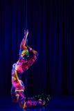 Ballerino femminile del palo nei colori al neon luminosi nell'ambito di ultravioletto Immagine Stock Libera da Diritti