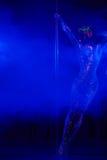 Ballerino femminile del palo nei colori al neon luminosi nell'ambito di ultravioletto Immagini Stock