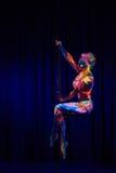 Ballerino femminile del palo nei colori al neon luminosi nell'ambito di ultravioletto Fotografia Stock