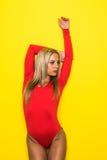 Ballerino relativo alla ginnastica della giovane donna esile bionda nell'ente rosso su fondo giallo Fotografie Stock Libere da Diritti