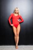 Ballerino relativo alla ginnastica della giovane donna esile bionda nell'ente rosso su fondo nero Fotografia Stock Libera da Diritti