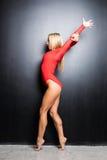 Ballerino relativo alla ginnastica della giovane donna esile bionda nell'ente rosso su fondo nero Fotografia Stock